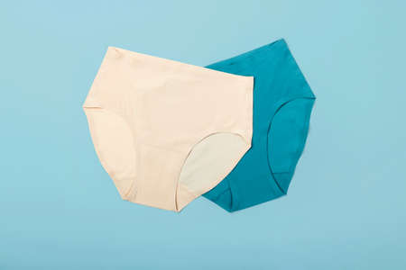 Women blue and beige panties on blue background. Minimal flat lay.