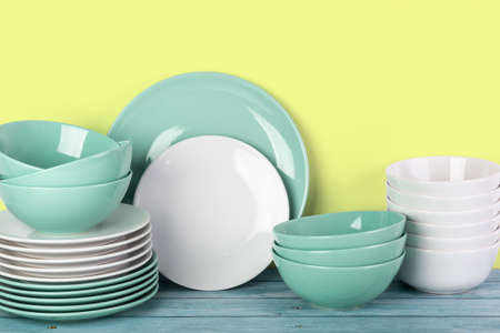 Sets of plates and bowls on kitchen shelf