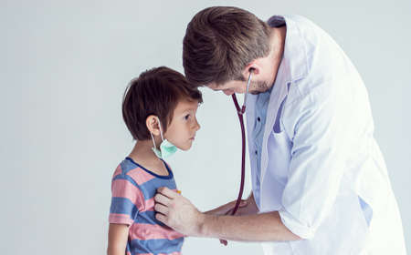Banner of handsome caucasian doctor examine a little boy who getting sick. There is a copy space on the left side