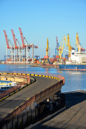 dockside: Dockside cranes, containers, containership, road to the sea on a background of blue sky