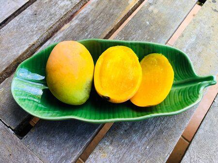 Ripe Mango tree (Mangifera caloneura Kurz) fruits in a green ceramic dish shaped banana leaf on wooden table, one cut in half
