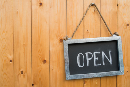 a signboard: Open Sign Hang On Wood Door Stock Photo