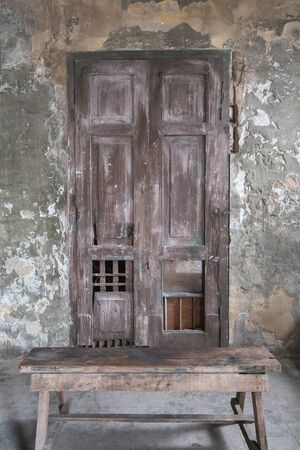 bangrak: Old wooden door in the wall of old building.