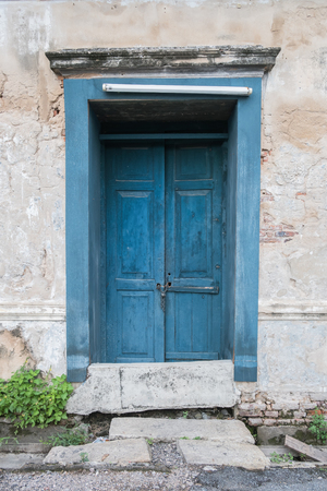 bangrak: Old wooden blue door in the wall of old building.