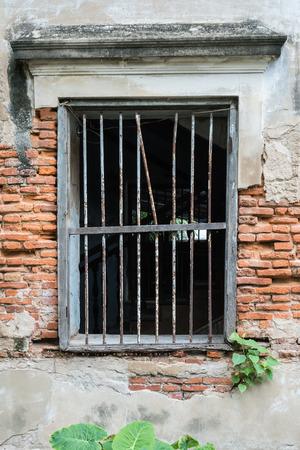 bangrak: Old metal lattice window in the wall of old building.