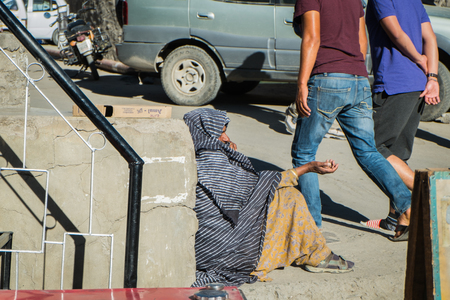 impoverished: Leh Ladakh,India - July 8,2014 : An unidentified poor beggar for money from a passerby in Leh.