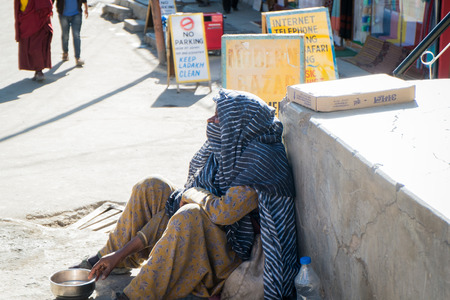 underdeveloped: Leh Ladakh,India - July 8,2014 : An unidentified poor beggar for money from a passerby in Leh.
