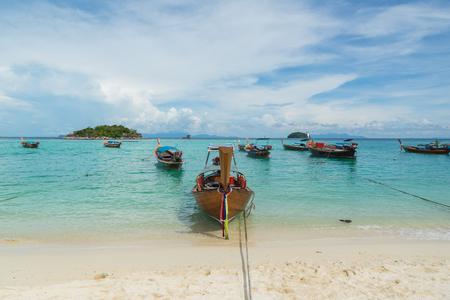 ko: Long tail boats lined along the beach with blue sky at Koh Lipe