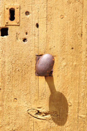 An old and rusty doorknob in the middle of a wooden door with a keyhole upside down at the top photo