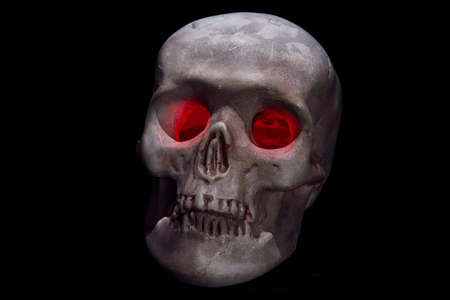 eye socket: A skull head with red eyes on black background