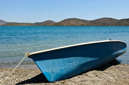 A blue boat lies on the beach on the dry photo