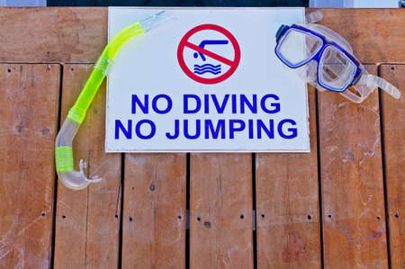 no diving sign: A no diving and no jumping sign with goggles and snorkel Stock Photo
