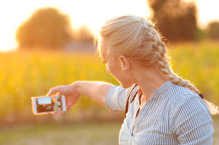 A young blond woman makes a selfie in the setting sun