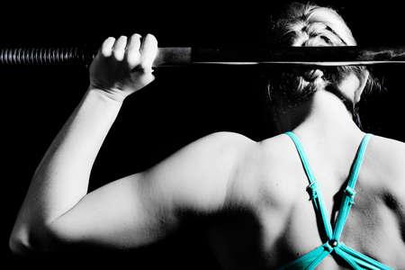Jonge atletische vrouw pompen spieren met barbell. zwart en wit