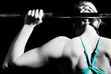 Young athletic woman pumping up muscles with barbell. black and white Stock Photo