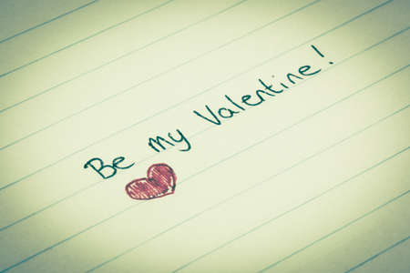 Be my valentine written on lined paper with a red colored heart
