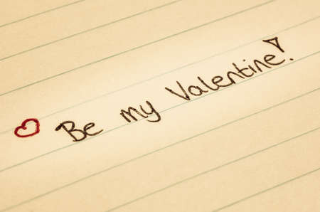 Be my valentine written on lined paper with a little heart