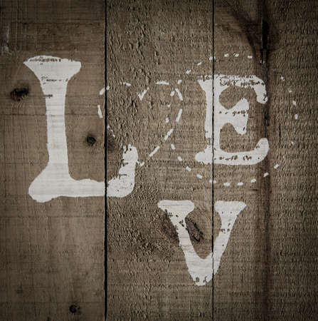 A background of wood with love text painted on it vignette Stock Photo