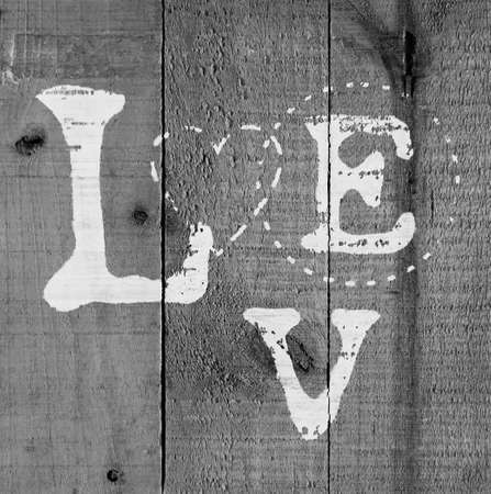 A background of wood with love text painted on it black and white Stock Photo