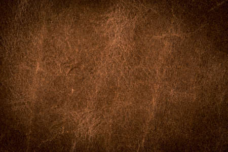 A background texture of brown colored leather vignette