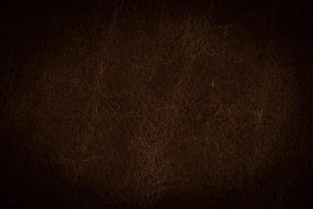 A background texture of dark brown colored leather vignette