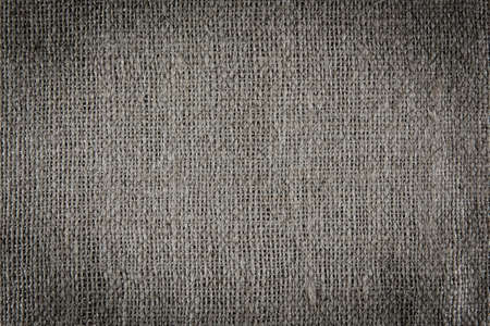 A background texture of burlap cloth dark vignette