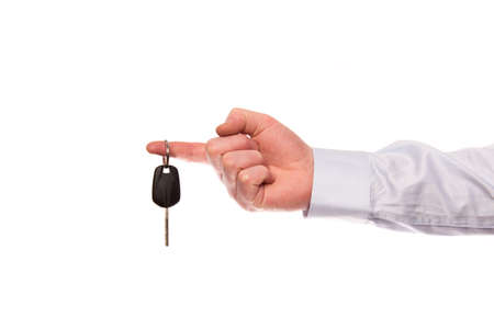 hold up: A hand of a businessman hold up a car key isolated on a white background