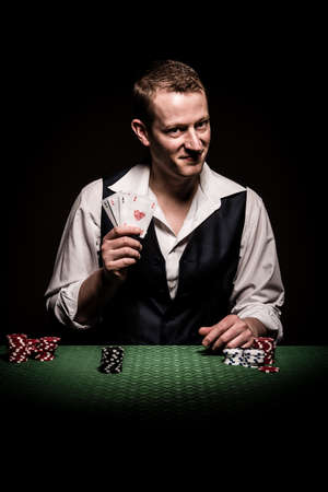 gambler: A male gambler smiling leaves four aces and winning hand