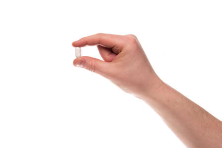 A hand of a man hold a pill between thumb and forefinger isolated on a white background