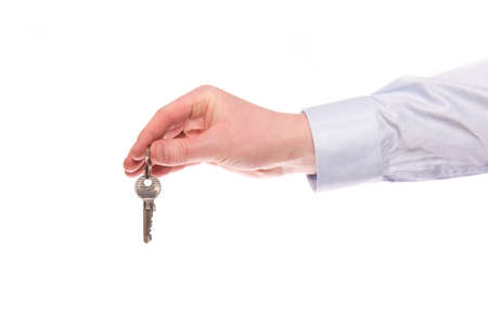 A hand of a businessman keep up a house key isolated on a white background Stock Photo