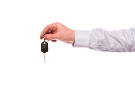 A hand of a businessman hold up a car key isolated on a white background photo