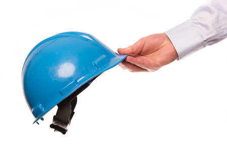 A hand of a businessman passes a safety helmet isolated on a white background