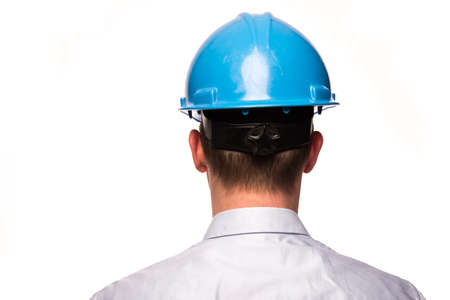 The backside of a buisiness man with a safety helmet isolated on a white background Stock Photo