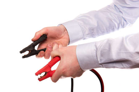 buisiness: A hand of a businessman hold two jumper cables up isolated on a white background