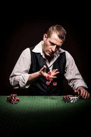 gambler: A male gambler rolls the dice in hopes to win Stock Photo