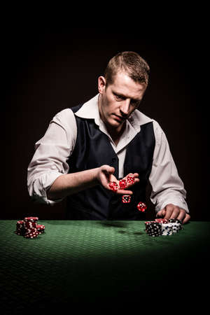 gambler: A male gambler rolls the dice after the betting