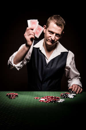 A male gambler is frustrated after losing and throw the cards away, showing movement