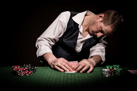 A male gambler checks once his cards on the table before placing the bet Stock Photo