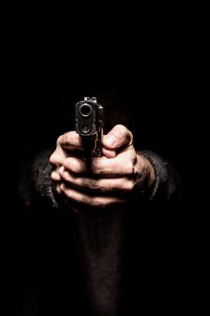 Dos manos apuntando una pistola hacia adelante, el concepto de amenaza, el peligro y la opresión