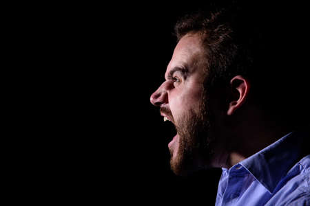 Bearded man screams into the dark Stock Photo - 52650104