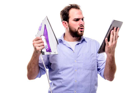 Man with iron and tablet searches for the manual, concept of women empowerment, clumsiness, household and online manuals