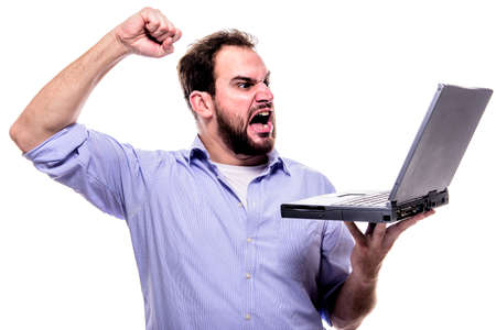 Bearded man shouting angrily at his laptop and waving his fist