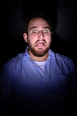 A bearded man screaming in the dark and has a frightened look on his face