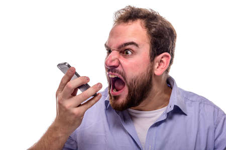 Bearded man shouting angrily into his mobile phone