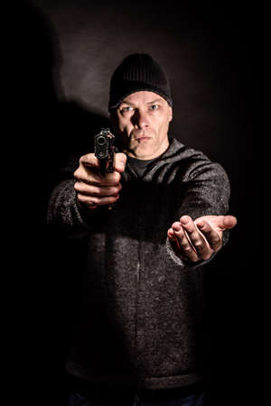 out of danger: Robber with a gun holds his hand out for the money, concept of danger, threat and extortion