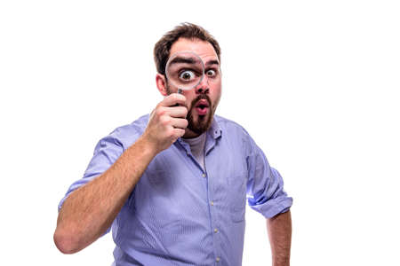 Funny business man looking surprised with magnifying glass