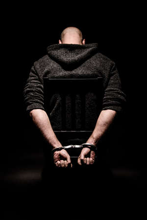 handcuffs: Man on chair in dark room sitting in handcuffs with head bowed Stock Photo