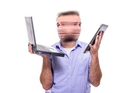 Un hombre de negocios con el caos en sus ojos tratando de realizar múltiples tareas con el ordenador portátil y la tableta al mismo tiempo, el concepto de estrés