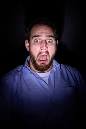 A bearded man screams and has a frightened look on his face Stock Photo - 52650175