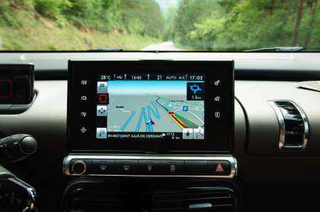 car navigation: Modern car navigation on the dashboard facing a winding road through the forest
